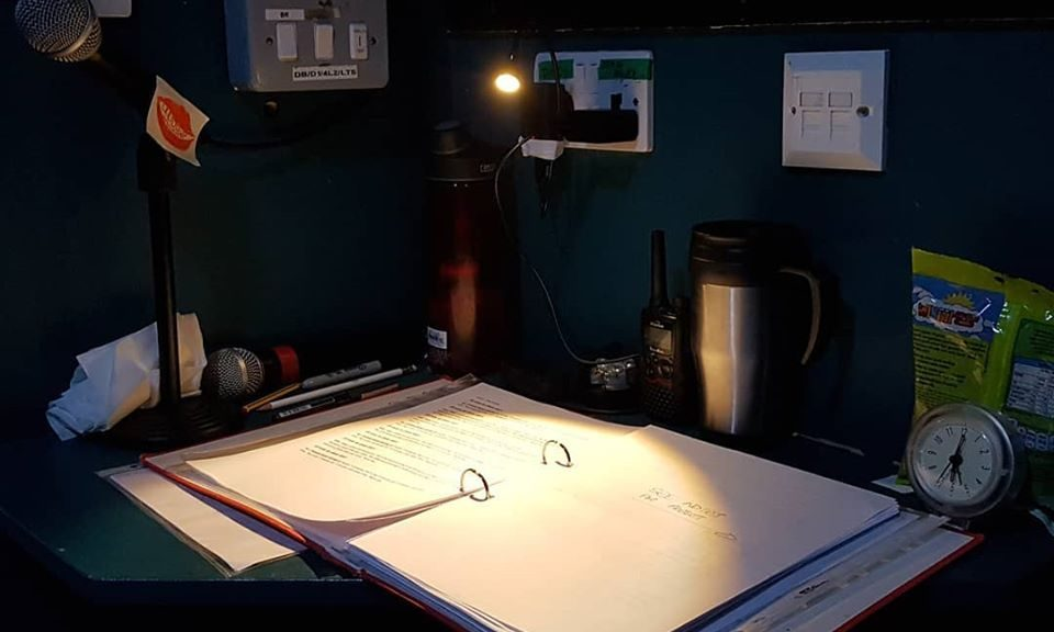 Stage management desk with folder, radio. water bottle, clock and coffee mug